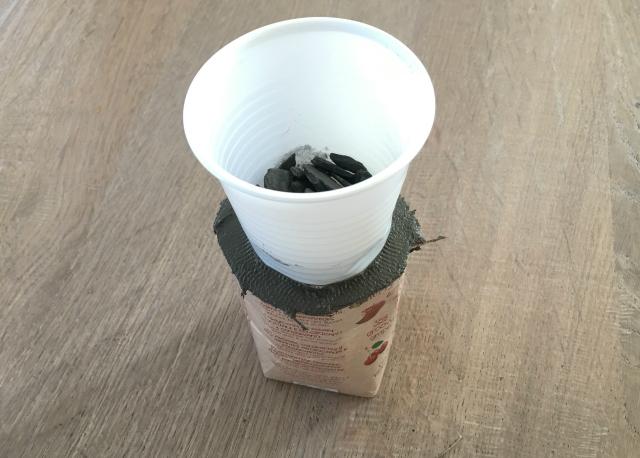 Zet dan je plastic bekertje op het cement in de verpakking. Dit vormt het gat voor het waxinelichtje.